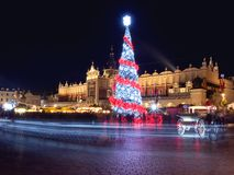 波兰、克拉科夫、主要集市广场和布料霍尔在冬天,在用圣诞树装饰的圣诞节市场期间 库存图片