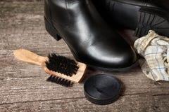 波兰奶油、刷子和黑鞋子 免版税库存照片