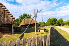 波兰,凯尔采 老波兰房子和桔槔在领域,画得好 免版税库存照片