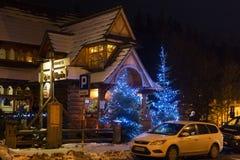 波兰,扎科帕内- 2015年1月03日:在街道上的传统木村庄房子在圣诞节装饰的扎科帕内 免版税库存图片
