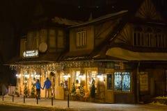 波兰,扎科帕内- 2015年1月03日:在街道上的传统木餐馆在圣诞节装饰的扎科帕内 免版税库存图片