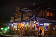 波兰,扎科帕内- 2015年1月03日:在街道上的传统木餐馆在圣诞节装饰的扎科帕内 免版税库存照片