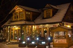 波兰,扎科帕内- 2015年1月03日:在街道上的传统木餐馆在圣诞节装饰的扎科帕内 库存图片