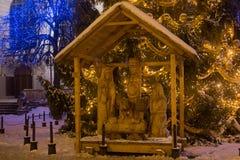 波兰,格但斯克- 2014年12月30日:在买多市场Dlugi Targ街道上的诞生场面在圣诞树附近的晚上 免版税库存图片