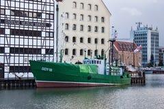 波兰,格但斯克- 2011年12月18日:在Motlawa河的绿色小船在中央海博物馆的历史建筑附近 库存图片