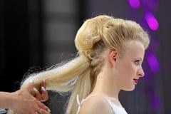 波兹南,波兰- 5月07 2016年:安排发型的美发师在T 免版税库存照片