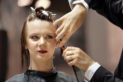 波兹南,波兰- 5月07 2016年:整理棕色头发w的美发师 库存照片