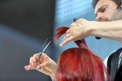 波兹南,波兰- 5月07 2016年:整理红色头发机智的美发师 库存照片