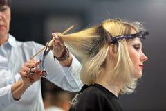 波兹南,波兰- 5月07 2016年:整理金发w的美发师 免版税库存照片