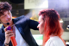 波兹南- 4月18 :安排发型的美发师使用喷发剂 免版税库存图片