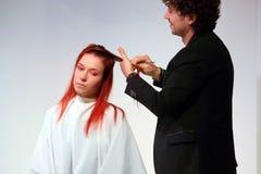 波兹南- 4月18 :整理有剪刀的美发师红色头发 图库摄影