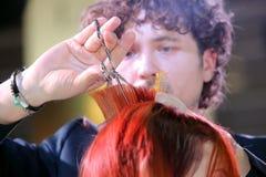 波兹南- 4月18 :整理有剪刀的美发师红色头发 库存照片