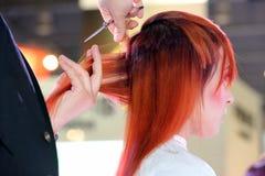 波兹南- 4月18 :整理有剪刀的美发师红色头发 免版税库存图片