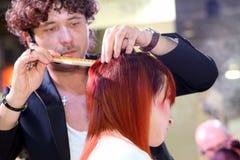 波兹南- 4月18 :整理有剪刀的美发师红色头发 免版税图库摄影