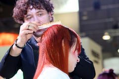 波兹南- 4月18 :整理有剪刀的美发师红色头发 库存图片