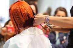 波兹南- 4月18 :整理有剪刀的美发师红色头发 免版税库存照片