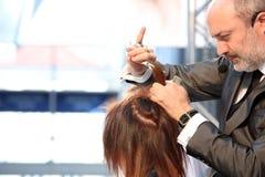 波兹南- 4月18 :整理棕色头发与的美发师剪 库存照片