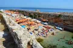 波利尼亚诺阿马雷,意大利- 2017年8月4日:与伞的小海滩拥挤了,普利亚,意大利 免版税库存照片