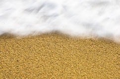 波动迷离和锋利的沙子在一个海滩在小希腊村庄 库存照片