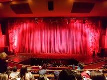 波哥大,哥伦比亚;2019å¹´4月13日:坐在colsubsidio剧院阶段的人们,在有红色帷幕的w el dorado街道附è 免版税库存照片