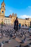 波哥大,哥伦比亚2017年10月22日:走在波利瓦的未认出的人民在美丽的蓝天摆正与数十 免版税库存照片