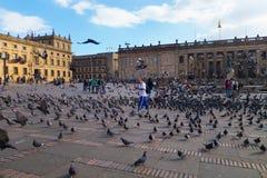 波哥大,哥伦比亚2017年10月22日:走在波利瓦的未认出的人民在美丽的蓝天摆正与数十 免版税库存图片