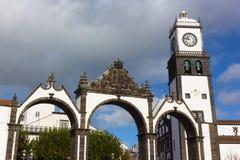 波塔斯角da Cidade门和圣徒Sabastian教会有钟楼的, Ponta Delgada,葡萄牙 免版税库存图片