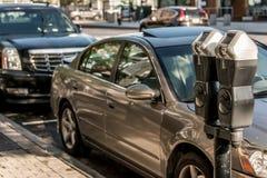 波士顿美国马萨诸塞在有偿的停车处的停车时间计时器在有汽车的街道在它后 图库摄影
