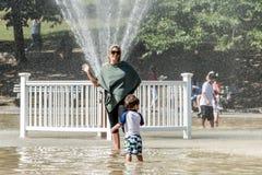 波士顿,麻省,美国06 09 2017 - 家庭孩子和人在热的夏日公园的青蛙池塘享用冷却喷头 免版税库存图片