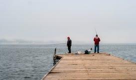 波尔图卢兹,斯洛文尼亚- 2015年10月17日:地方渔夫从码头钓鱼 在这些标尺的手上 库存照片
