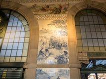 波尔图,葡萄牙-圣本托与美丽的azulejos蓝色瓦片的火车站内部在描述历史的场面的墙壁上 库存图片