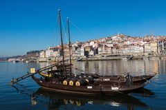 波尔图,葡萄牙- 1月18,2018 :运载桶波尔图酒看的相接的小船在河岸 在波尔图, Duoro的全景视图 免版税库存照片