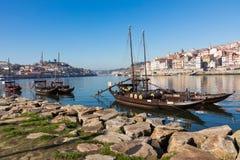 波尔图,葡萄牙- 1月18,2018 :运载桶波尔图酒看的相接的小船在河岸 在波尔图, Duoro的全景视图 库存图片