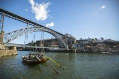波尔图,葡萄牙- Ribeira,在杜罗河河的传统小船在老镇, Luiz铁桥梁在背景中 图库摄影