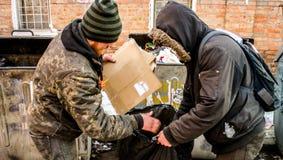 波尔塔瓦,乌克兰- 2016年2月18日:在垃圾箱附近的两个年轻人收集回收的纸 库存图片