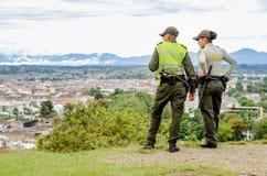 波帕扬,哥伦比亚- 2018年2月06日:佩带一致的警察和享受看法的室外观点的未认出的人民 库存照片