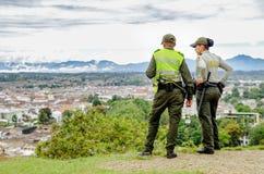 波帕扬,哥伦比亚- 2018年2月06日:佩带一致的警察和享受看法的室外观点的未认出的人民 库存图片