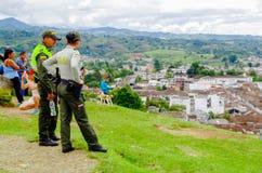 波帕扬,哥伦比亚- 2018年2月06日:佩带一致的警察和享受看法的室外观点的未认出的人民 免版税库存图片