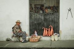 波帕扬,哥伦比亚- 2018年3月31日:的妇女卖在白色殖民地大厦街道的室外观点handycrafts  免版税库存图片