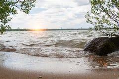 波浪冲对含沙岸 日落 库存图片