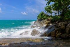 波浪击中了在蓝色海的岸的岩石 免版税库存图片