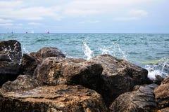 波浪击中了巨大的石头 在背景中,有许多 库存图片