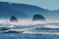 波浪和峭壁反对山 免版税库存图片