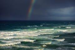 波浪在有风雨如磐的云彩和彩虹的风大浪急的海面 免版税图库摄影