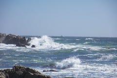 波浪在沿17英里驱动加利福尼亚的岩石碰撞 免版税库存照片