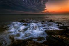 波浪在海滩打了在日落 库存图片