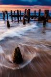 波浪在特拉华湾的码头打桩附近打旋在日落, s 库存图片