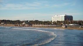 波浪在离开的海滩滚动在黑暗的树和高旅馆附近 股票录像