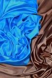 波浪折叠蓝色和棕色丝绸缎布料构造背景 免版税库存照片