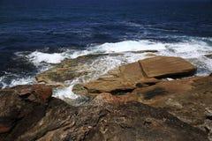 波浪抚摸的精采岩石 库存照片